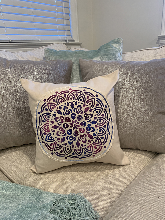 medallion stenciled pillow sitting on couch