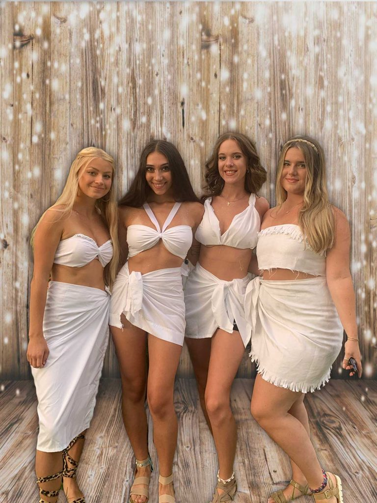 girls in two piece togas in front  of a wood wall with lights