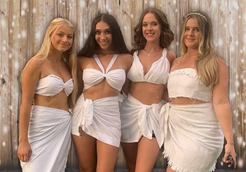 four girls in two piece togas in front of a wood wall with lights