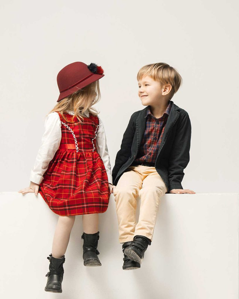 A girl dressed in a red plaid dress looking at a smiling boy in a blazer and tan pants both sitting