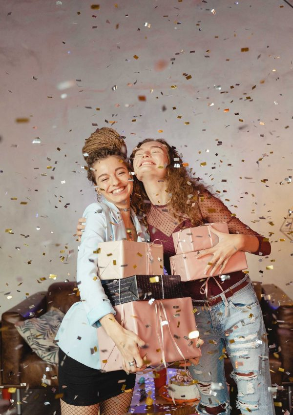 two girls smiling holding presents with confetti falling