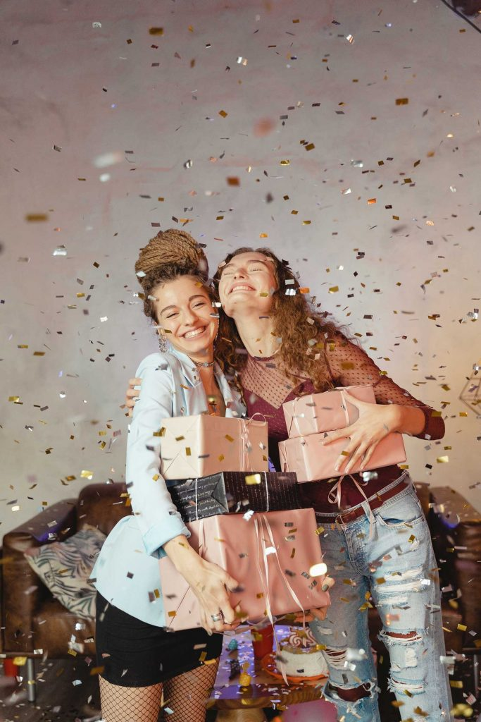 two teens smiling holding presents with confetti falling