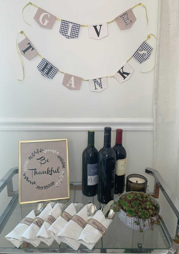 give thanks paper banner on gold ribbon, gold frames be thankful art with 6 napkin gratitude holders on a bar cart