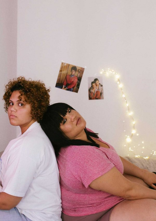 two teens sitting back to back in a room with lights and photos on the wall
