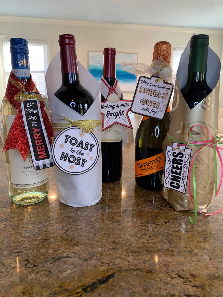 5 wine bottles on a counter with paper tags and w ribbon