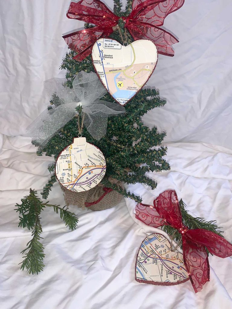 three nyc subway map ornaments with red and white ribbons on display on small xmas tree