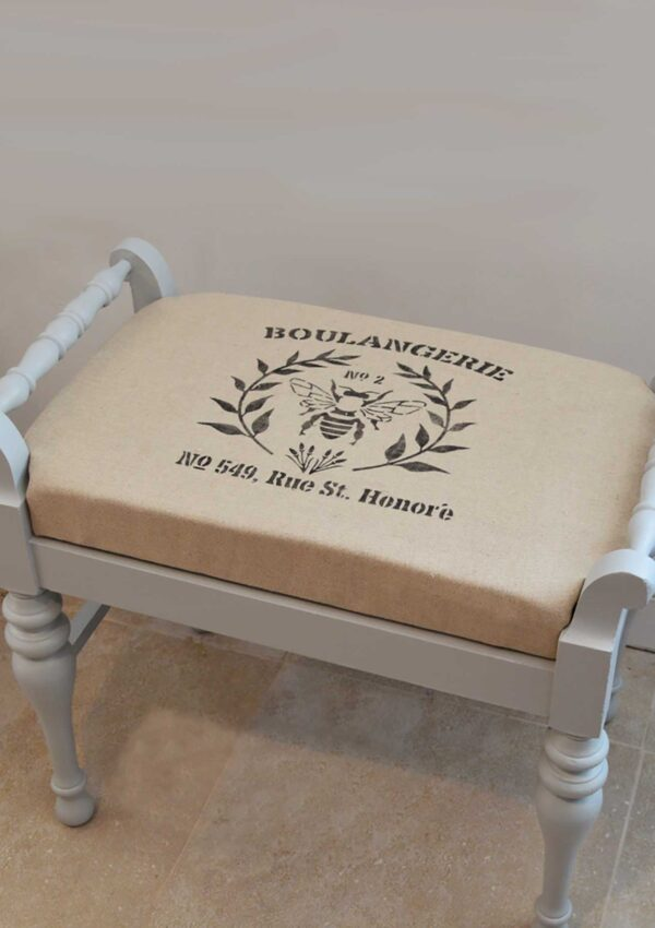 upholstered painted grey bench with stencil on cushion that reads Boulangerie no 549 rue st. Honoré with a bee and leaf graphic in center
