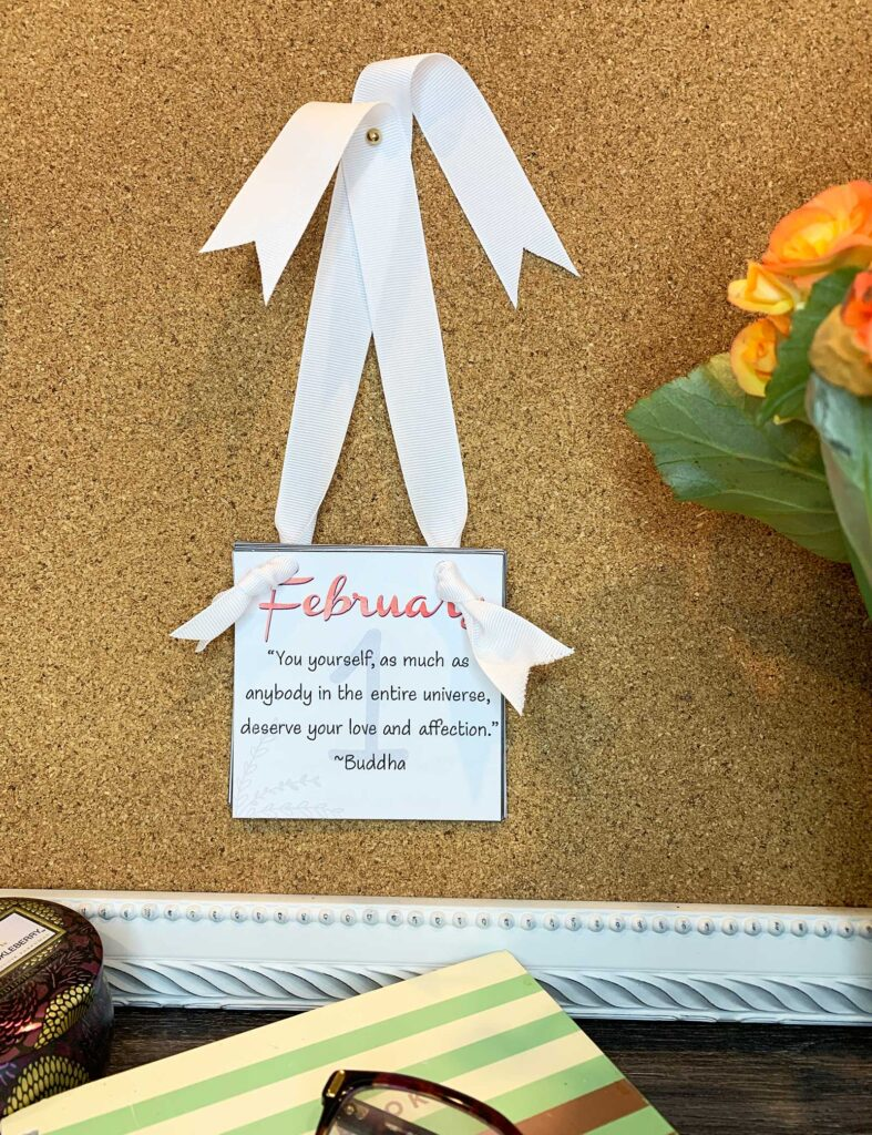 February motivational calendar tied with white ribbon and tacked to a bulletin board.