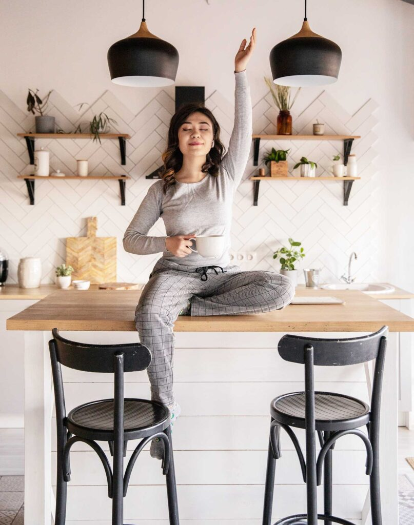 women sitting on kitchen counter in pajamas holding a cup of coffee