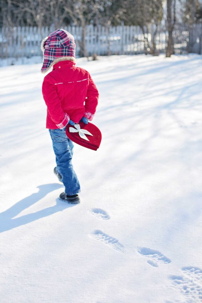 toddler boy in plaid hat walking away in the snow holding a heart box of valentines day candies