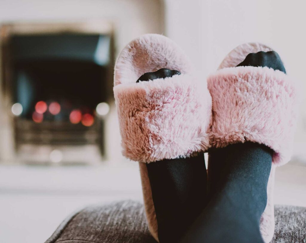 pink fuzzy slippers on black socked feet  in front of a fireplace