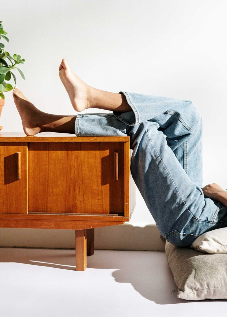 woman with legs up on a credenza in wide leg jeans