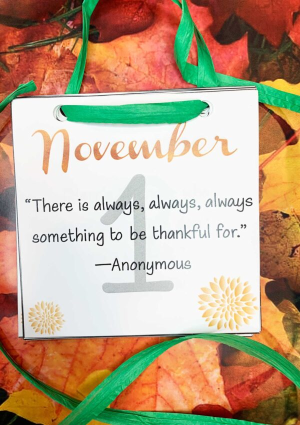 november inspirational calendar with a green ribbon on fall leaves