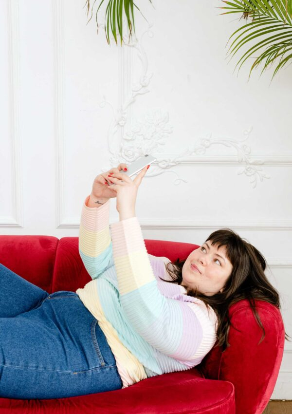 plus size teen on couch looking at phone